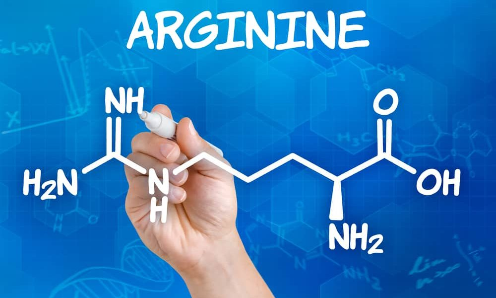Hand with pen drawing the chemical formula of arginine