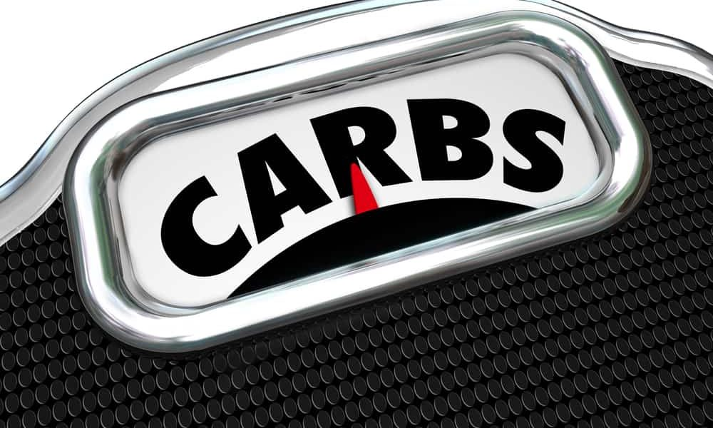 Carbs word on a scale to illustrate eating too much carbohydrates in your diet and needing to cut on snack food and lose weight