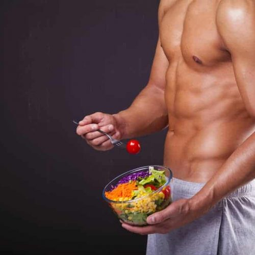 Fit man holding a bowl of fresh salad on grunge background