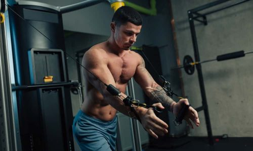 Young strong man in gym doing chest cable workout with high intensity